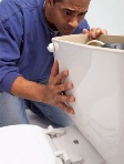 Man looking at toilet small