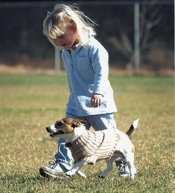 Little girl running with a small dog
